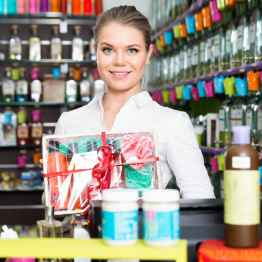Polite attractive  cheerful positive smiling salesgirl offering cosmetic gift set in perfume shop